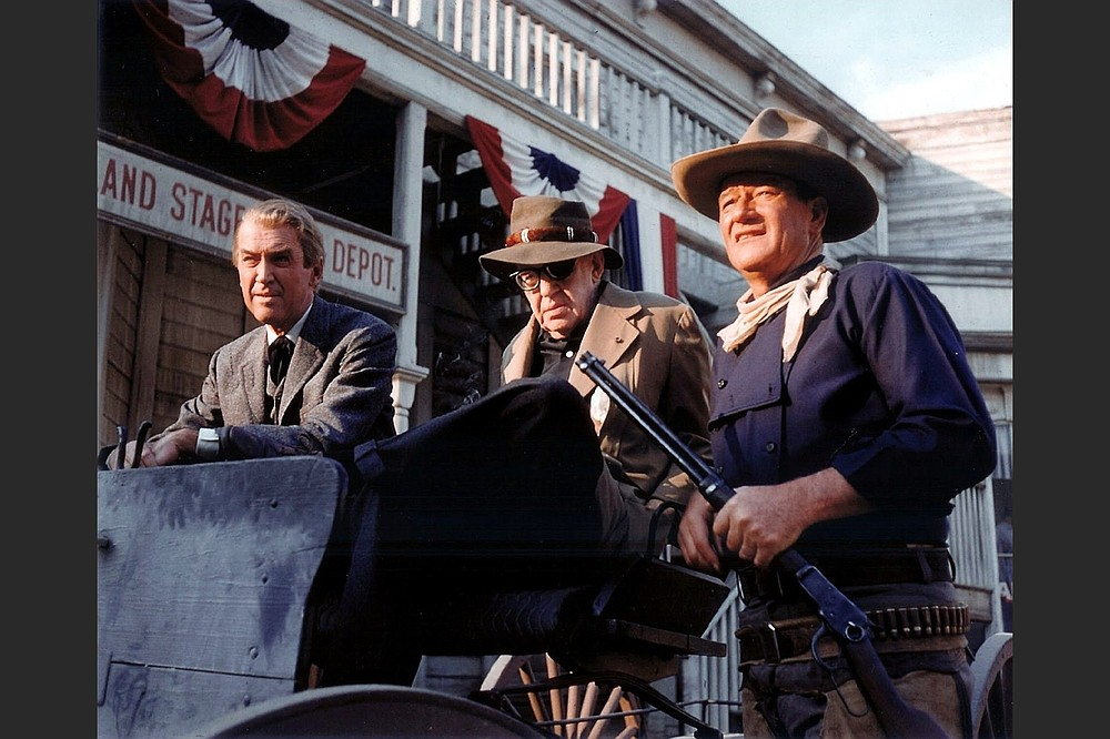 """John Wayne (right) takes five behind the scenes with Jimmy Stewart and director John Ford on the set of """"The Man Who Shot Liberty Valance"""" (1962)."""
