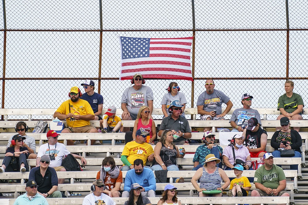 Fans look on from the stands as some are still wearing mask and others are not during a NASCAR Cup Series auto race at Dover International Speedway, Sunday, May 16, 2021, in Dover, Del. (AP Photo/Chris Szagola)