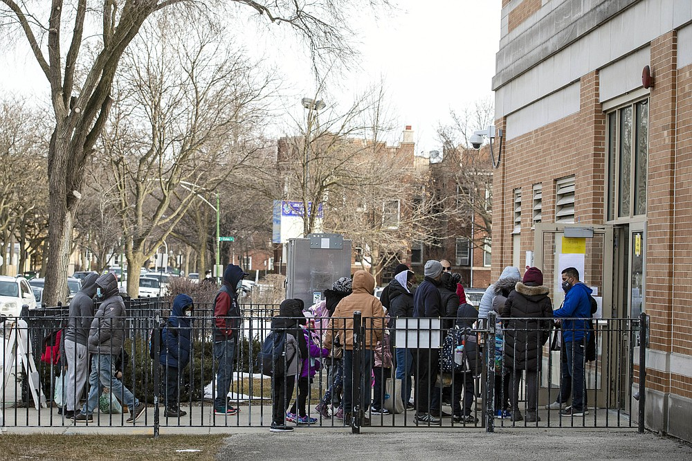 FILE - In this March 1, 2021, file photo, parents and children line up outside George B. Armstrong International Studies Elementary School, as students return to in-person learning at the Rogers Park neighborhood school on the North Side of Chicago. Children are having their noses swabbed or saliva sampled at school to test for the coronavirus in cities such as Baltimore, New York and Chicago. As more children return to school buildings this spring, widely varying approaches have emerged on how and whether to test students and staff members for the virus. (Ashlee Rezin Garcia/Chicago Sun-Times via AP, File)