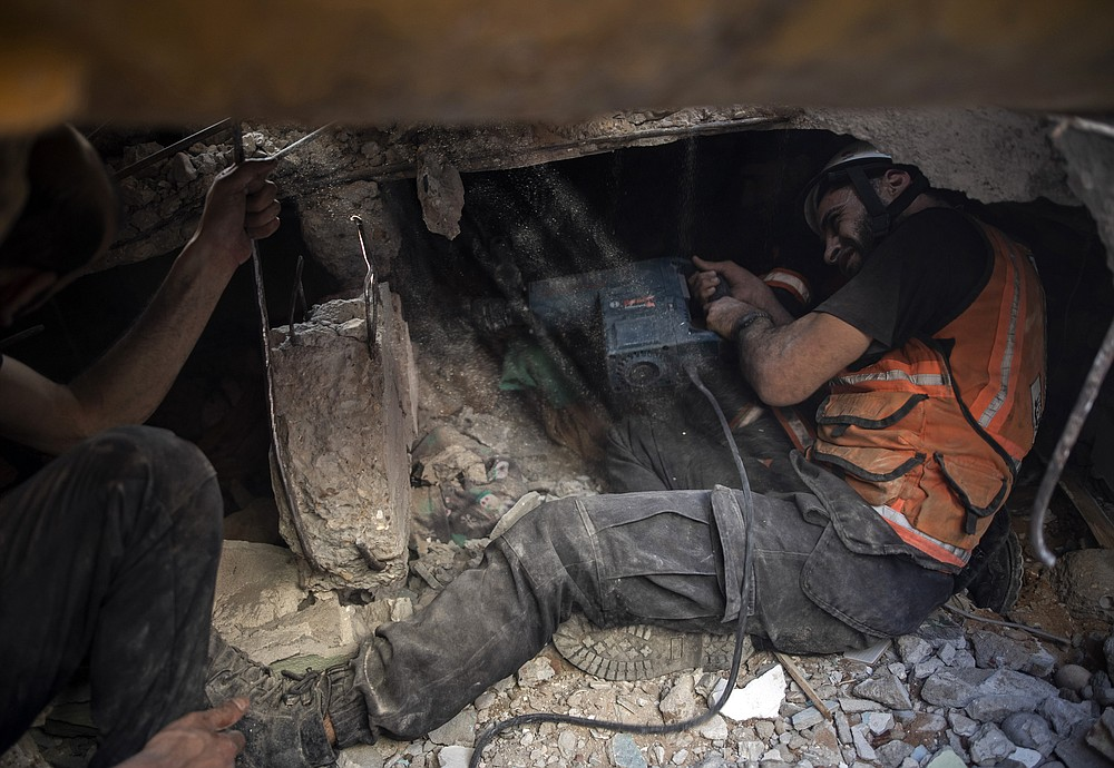 Palestinian rescuers look for survivors under the rubble of a destroyed building following deadly Israeli airstrikes in Gaza City, Sunday, May 16, 2021. The airstrikes flattened three buildings and killed at least 26 people Sunday, medics said, making it the deadliest single attack since heavy fighting broke out between Israel and the territory's militant Hamas rulers nearly a week ago. (AP Photo/Khalil Hamra)
