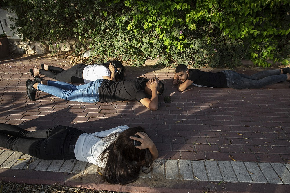 Israelis take cover as a siren sounds a warning of incoming rockets fired from the Gaza Strip, in Ashkelon, southern Israel, Sunday, May 16, 2021. (AP Photo/Heidi Levine)