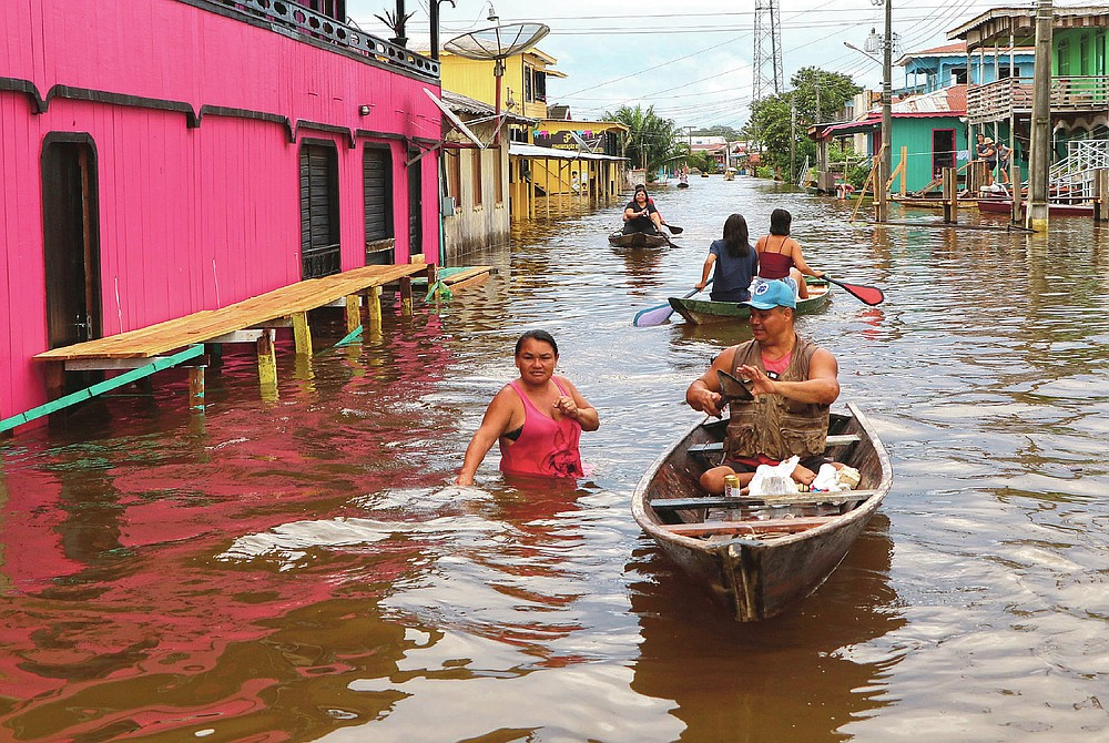 Residents navigate flooded streets in Anama, Amazonas state, Brazil, Thursday, May 13, 2021.  (AP Photo/Edmar Barros)