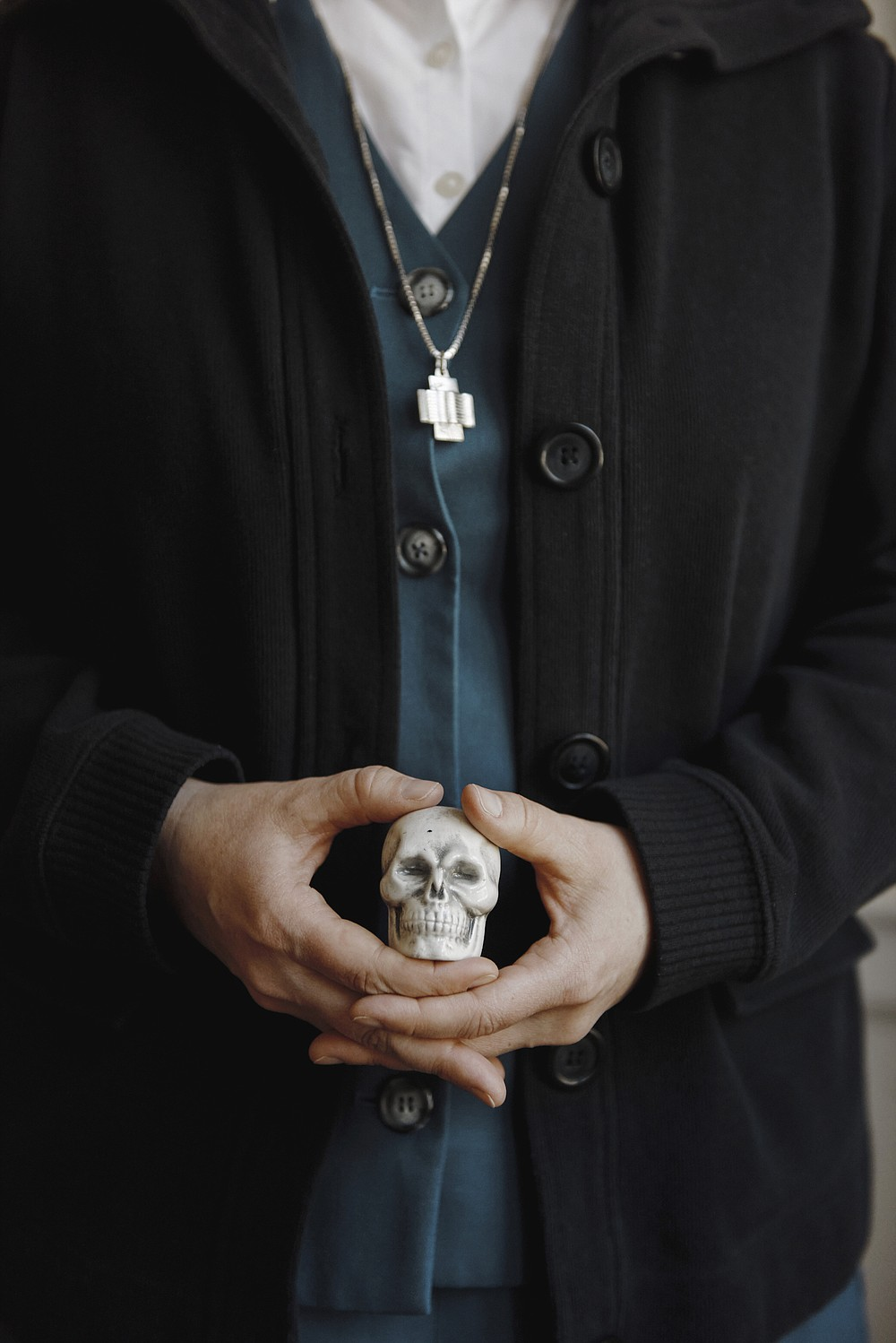 """Sister Theresa Aletheia Noble holds a small sculpture of a skull at Daughters of St. Paul convent in Boston, May 12, 2021. Since 2017, Sister Aletheia has made it her mission to revive the practice of memento mori, a Latin phrase meaning """"Remember your death,"""" which encourages intentional thought about one's death every day as a means of appreciating the present and focusing on the future. (Tony Luong/The New York Times)"""