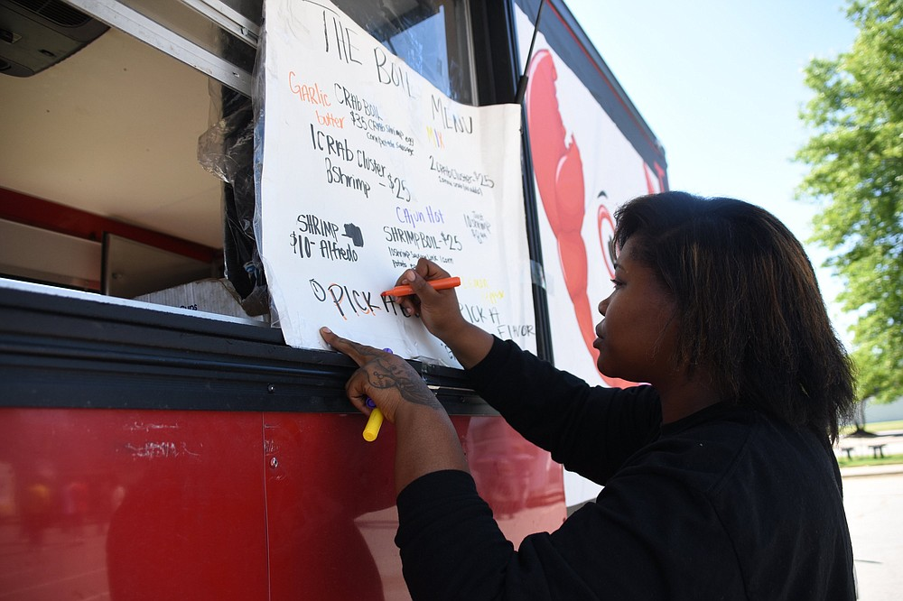 Renea Daniels, co-owner of The Boil, adds details to the menu for Food Truck Friday on May 14 at Simmons Bank Arena in North Little Rock. The food truck will be part of this week's lineup as well. (Arkansas Democrat-Gazette/Staci Vandagriff)