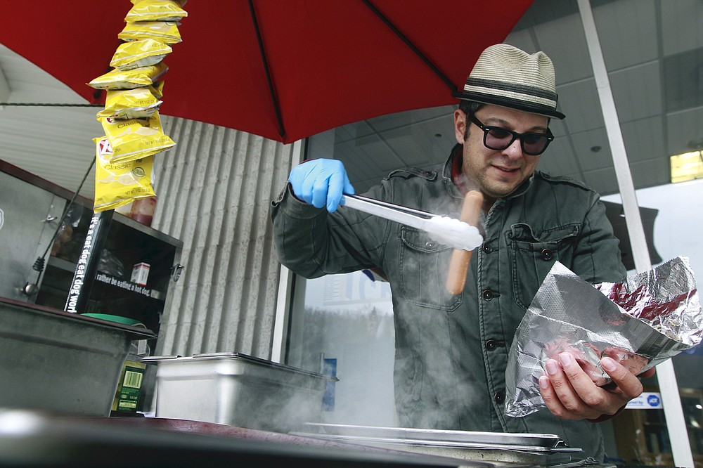 Mike Juiliano, aka Hot Dog Mike, serves up a hot dog in 2013. Juiliano, who has been living in North Carolina, will be back in Little Rock for a benefit June 18-19. (Democrat-Gazette file photo)