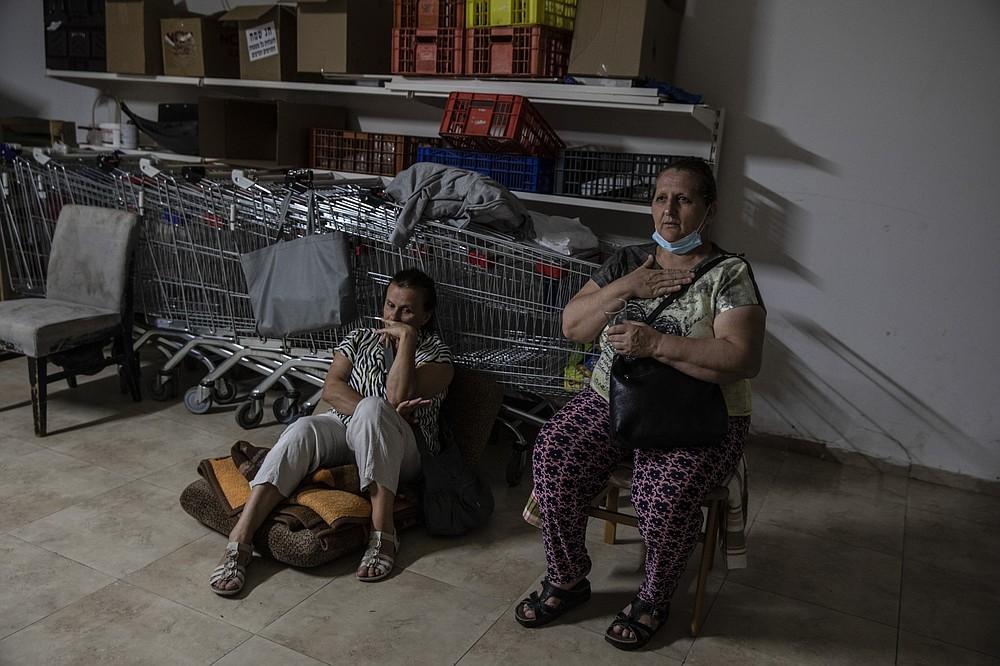 Israeli Kassadra Bodari, left, and Lilian Feciouru take shelter in Ashdod, Israel during sirens warning of incoming rockets fired from Gaza Strip, Tuesday, May 18, 2021. (AP Photo/Heidi Levine)