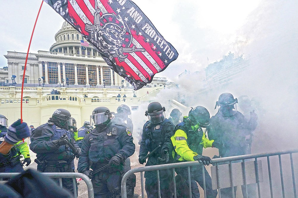 FILE - In this Jan. 6, 2021, file photo, police try to hold off supporters of then-President Donald Trump who tried to break through a police barrier, at the Capitol in Washington. (AP Photo/Julio Cortez, File)