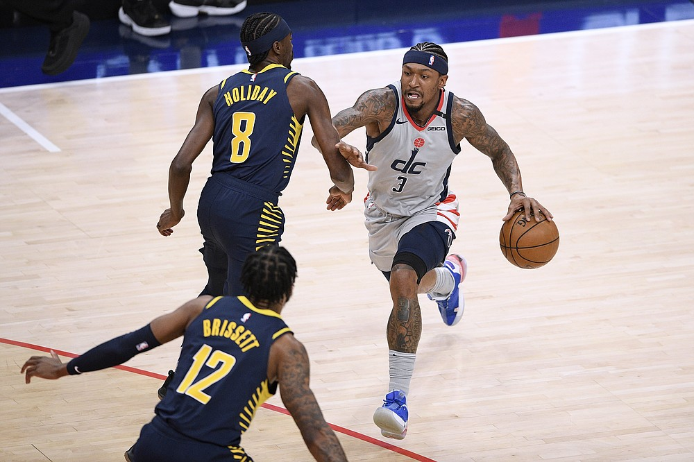 Washington Wizards guard Bradley Beal (3) dribbles the ball as Indiana Pacers forward Justin Holiday (8) and forward Oshae Brissett (12) defend during the first half of an NBA basketball Eastern Conference play-in game Thursday, May 20, 2021, in Washington. (AP Photo/Nick Wass)