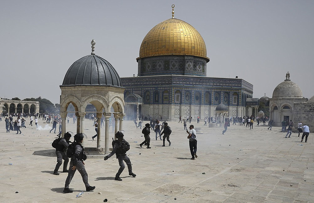 Palestinians run from concussion grenades thrown by Israeli police Friday in front of the Dome of the Rock in the al-Aqsa Mosque compound in Jerusalem. Clashes at the mosque earlier this month were a main trigger in the 11-day conflict that just ended. (AP/Mahmoud Illean)
