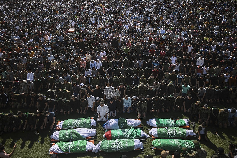 Palestinians pray by the bodies of members of the Izzedine al-Qassam Brigades, the military wing of Hamas movement, who died in Israeli bombardment of a tunnel, during their funeral in Khan Younis, southern Gaza Strip, Friday, May 21, 2021. A cease-fire took effect early Friday after 11 days of heavy fighting between Israel and Gaza's militant Hamas rulers that was ignited by protests and clashes in Jerusalem. (AP Photo/Yousef Masoud)