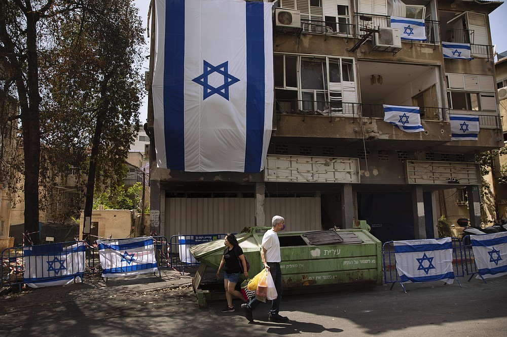 People walk by a residential building covers with Israeli flags after last week it was hit by a rocket fired from the Gaza Strip, in Ramat Gan, central Israel, Friday, May 21, 2021. A cease-fire took effect early Friday after 11 days of heavy fighting between Israel and Gaza's militant Hamas rulers that was ignited by protests and clashes in Jerusalem. (AP Photo/Oded Balilty)