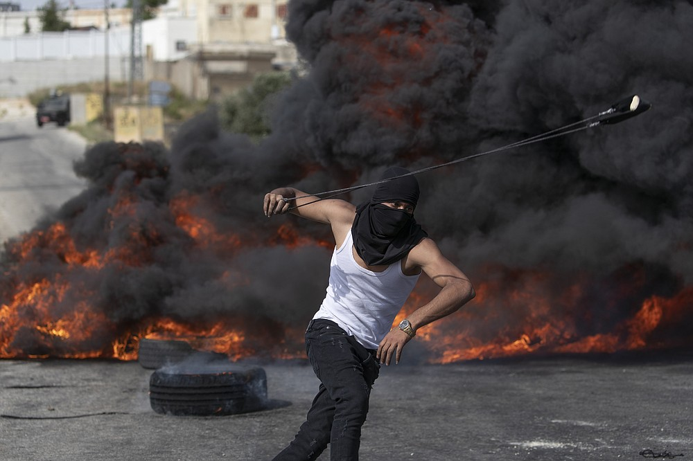 A Palestinian protester uses a slingshot during clashes with Israeli soldiers at the northern entrance of the West Bank city of Ramallah, Friday, May 21, 2021. A cease-fire took effect early Friday after 11 days of heavy fighting between Israel and Gaza's militant Hamas rulers that was ignited by protests and clashes in Jerusalem. (AP Photo/Nasser Nasser)