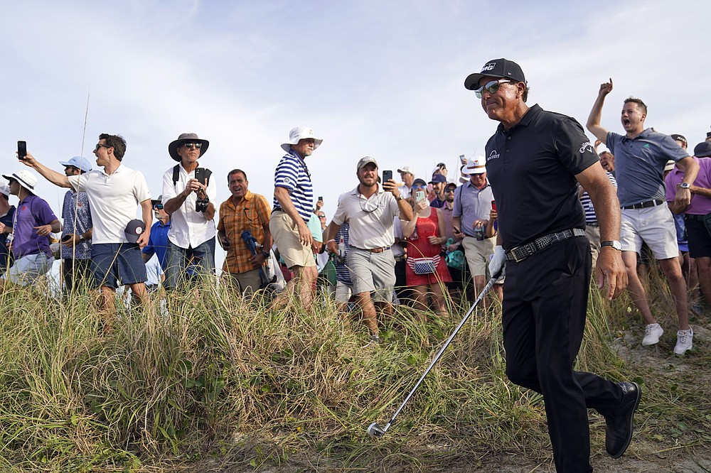 Fans cheer after Phil Mickelson hit his second shot on the 16th hole from the rough during the third round at the PGA Championship golf tournament on the Ocean Course, Saturday, May 22, 2021, in Kiawah Island, S.C. (AP Photo/David J. Phillip)