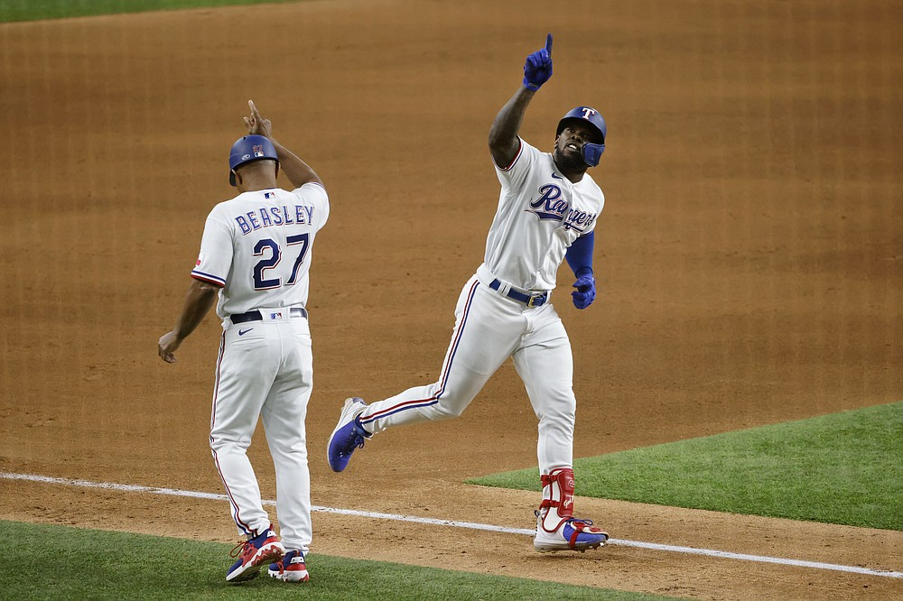 Texas Rangers' Adolis Garcia, right, celebrates his second solo home run with third base coach Tony Beasley (27) during the seventh inning of a baseball game against the Houston Astros, Saturday, May 22, 2021, in Arlington, Texas. (AP Photo/Michael Ainsworth)