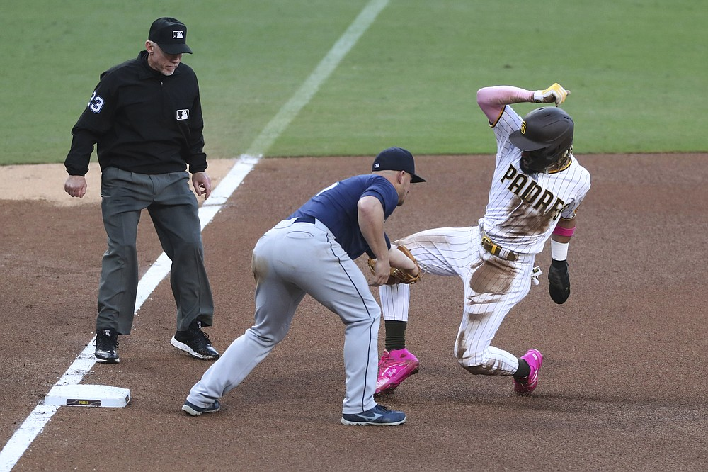 San Diego Padres' Fernando Tatis Jr. is tagged out by Seattle Mariners' Kyle Seager on an attempted steal of third during the fourth inning of a baseball game Saturday, May 22, 2021, in San Diego. (AP Photo/Derrick Tuskan)