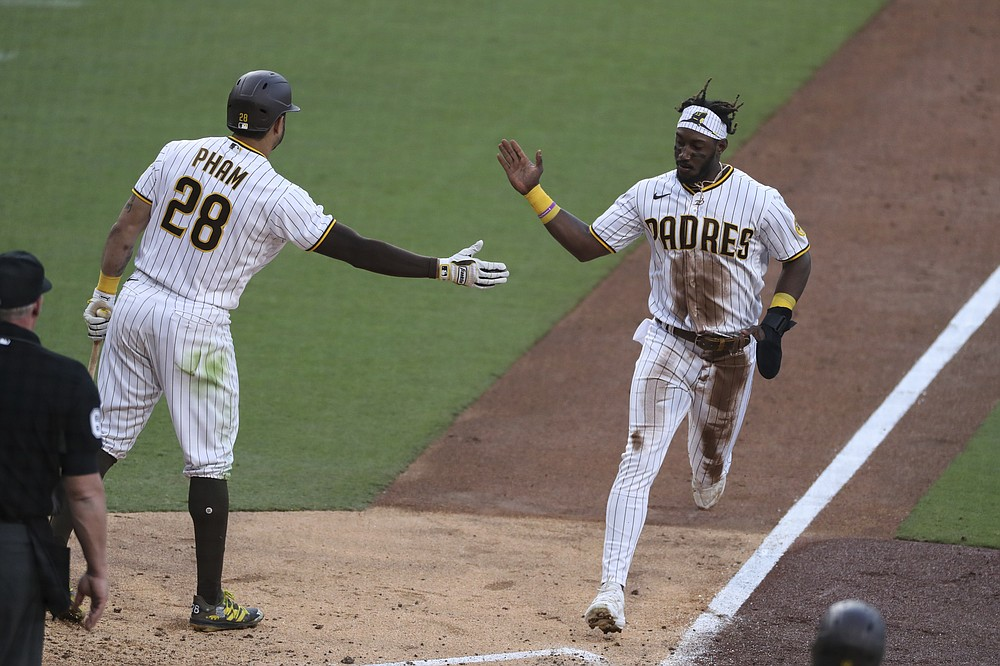 San Diego Padres' Jorge Mateo, right, is congratulated by Tommy Pham (28) on a steal of third base and scoring on a throwing error by Seattle Mariners catcher Tom Murphy during the fifth inning of a baseball game Saturday, May 22, 2021, in San Diego. (AP Photo/Derrick Tuskan)