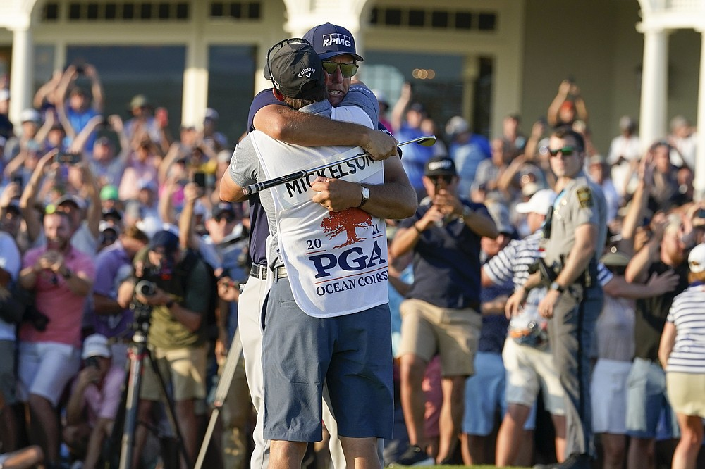 Phil Mickelson embraces his caddie after winning the final round at the PGA Championship golf tournament on the Ocean Course, Sunday, May 23, 2021, in Kiawah Island, S.C. (AP Photo/Matt York)