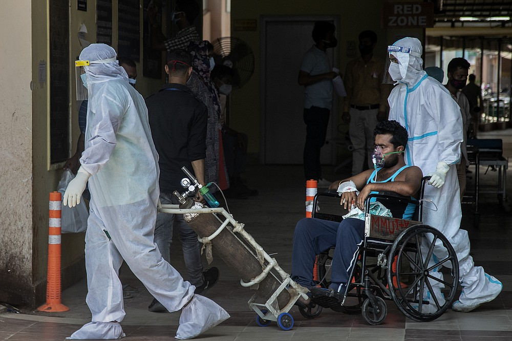 Health workers in protective suits shift a COVID-19 patient at a government hospital in Gauhati, India, Monday, May 24, 2021. India crossed another grim milestone Monday of more than 300,000 people lost to the coronavirus as a devastating surge of infections appeared to be easing in big cities but was swamping the poorer countryside. (AP Photo/Anupam Nath)