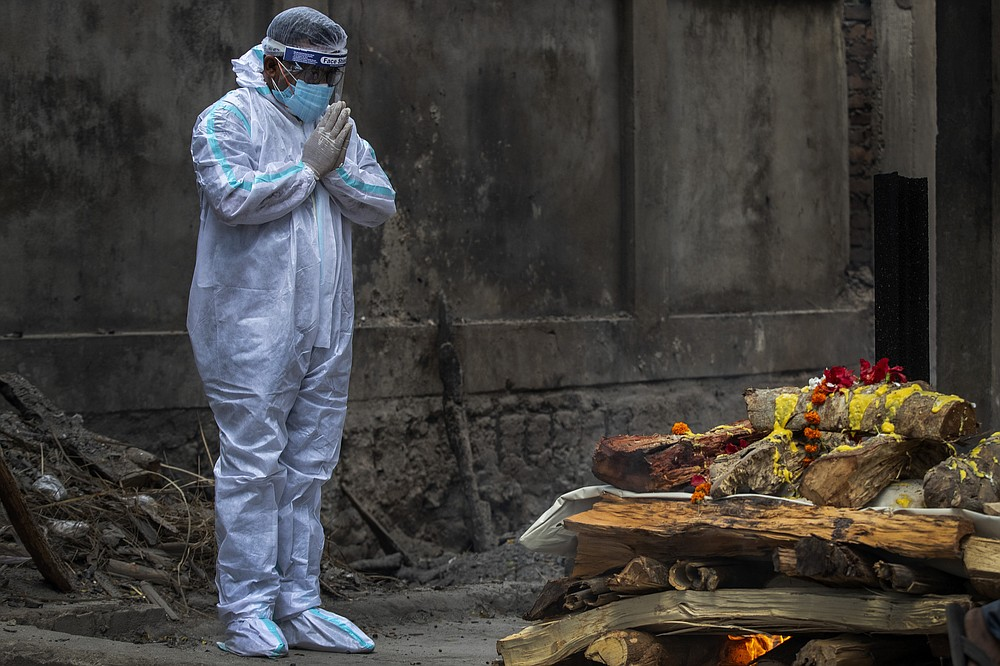 A relative in protective suit performs last rituals as the body of a person who died of COVID-19 is cremated in Gauhati, India, Monday, May 24, 2021. India crossed another grim milestone Monday of more than 300,000 people lost to the coronavirus as a devastating surge of infections appeared to be easing in big cities but was swamping the poorer countryside. (AP Photo/Anupam Nath)