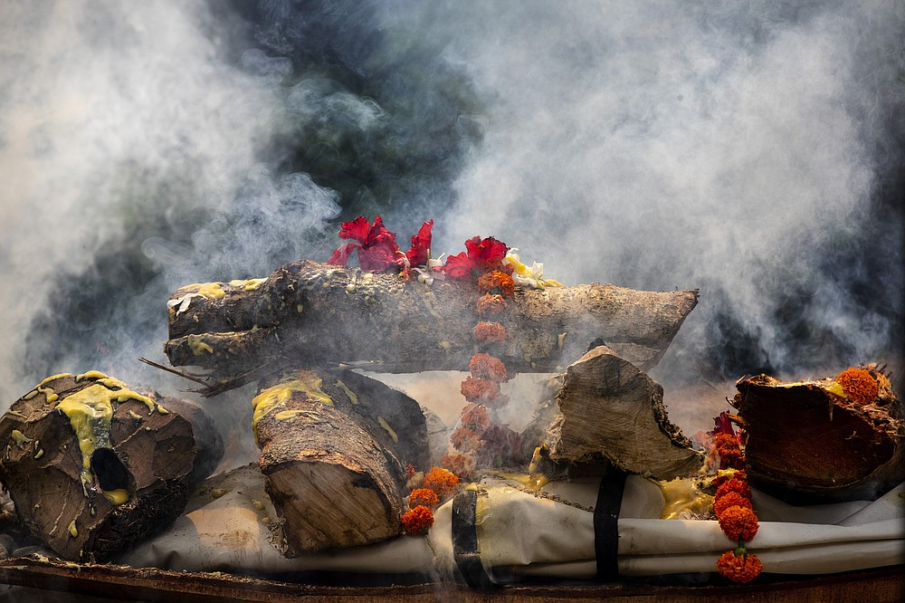 The body of a person who died of COVID-19 is cremated in Gauhati, India, Monday, May 24, 2021. India crossed another grim milestone Monday of more than 300,000 people lost to the coronavirus as a devastating surge of infections appeared to be easing in big cities but was swamping the poorer countryside. (AP Photo/Anupam Nath)