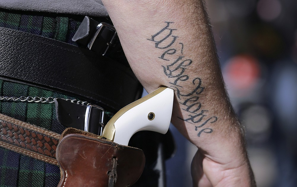 FILE - In this Jan. 26, 2015 file photo, a supporter of open carry gun laws, wears a pistol as he prepares for a rally in support of open carry gun laws at the Capitol, in Austin, Texas. Texas lawmakers have given final approval to allowing people carry handguns without a license, and the background check and training that go with it. The Republican-dominated Legislature approved the measure Monday, May 24, 2021 sending it to Gov. Abbott. (AP Photo/Eric Gay, File)