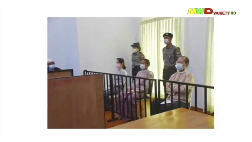 In this image from Myawaddy TV, a photograph shown during a news report showing the appearance of deposed Myanmar leader Aung San Suu Kyi, former President Win Myint, sitting 3rd from right, and former Naypyitaw Council chairman Dr. Myo Aung before a special court, shown while a report about Suu Kyi's case is read by a news presenter Monday, May 24, 2021, in Naypyitaw, Myanmar.  Myanmar's ousted leader Aung San Suu Kyi has made a court appearance in person for the first time since the military arrested her Feb. 1. (Myawaddy TV via AP)