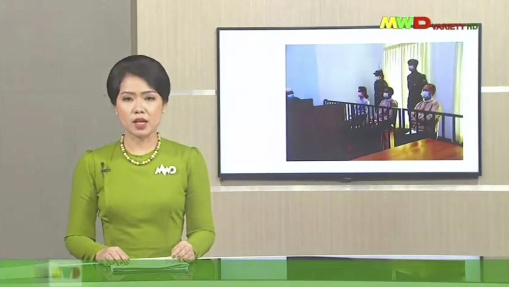 In this image from Myawaddy TV, a photograph of deposed Myanmar leader Aung San Suu Kyi's court appearance was shown during a report about her case is read by a news presenter Monday, May 24, 2021, in Naypyitaw, Myanmar.  Myanmar's ousted leader Aung San Suu Kyi has made a court appearance in person for the first time since the military arrested her Feb. 1. (Myawaddy TV via AP)