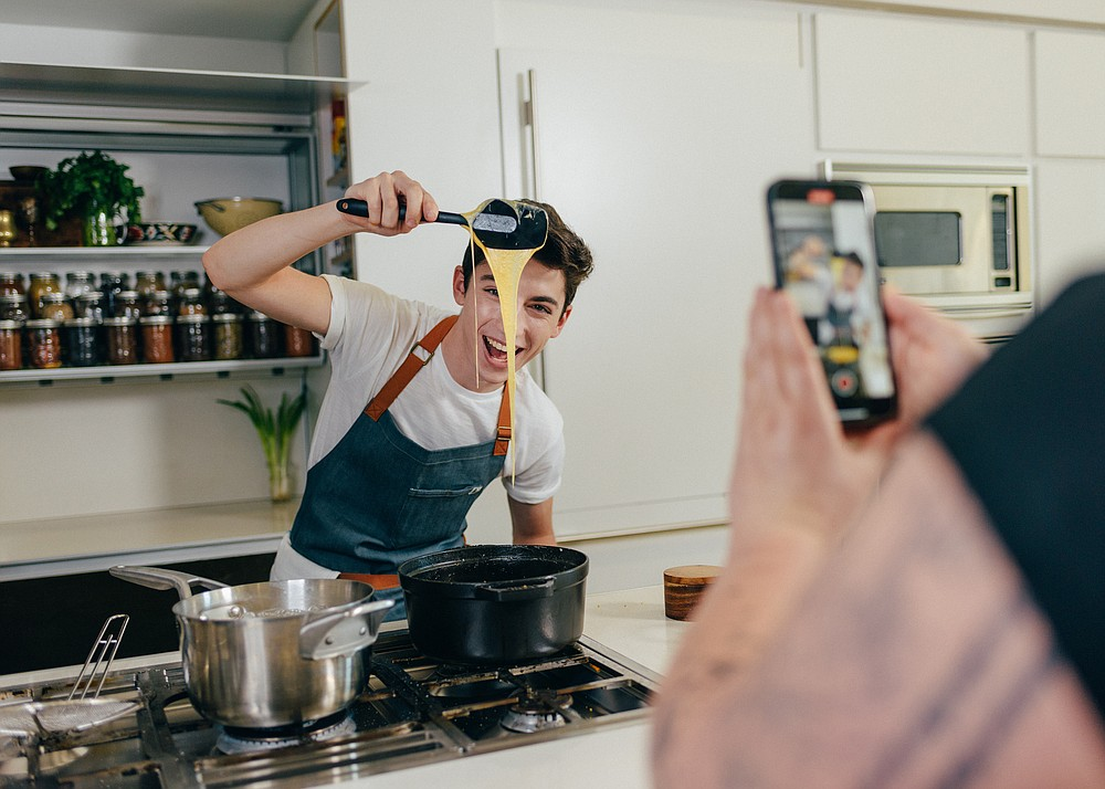 """Eitan Bernath, a 19-year-old TikTok star with more than 1.6 million followers, films a cooking video at his home in New York, May 17, 2021. """"TikTok is the biggest thing that happened to me in my career, and honestly the reason why I am where I am today,"""" said Bernath. (The New York Times/Timothy O'Connell)"""