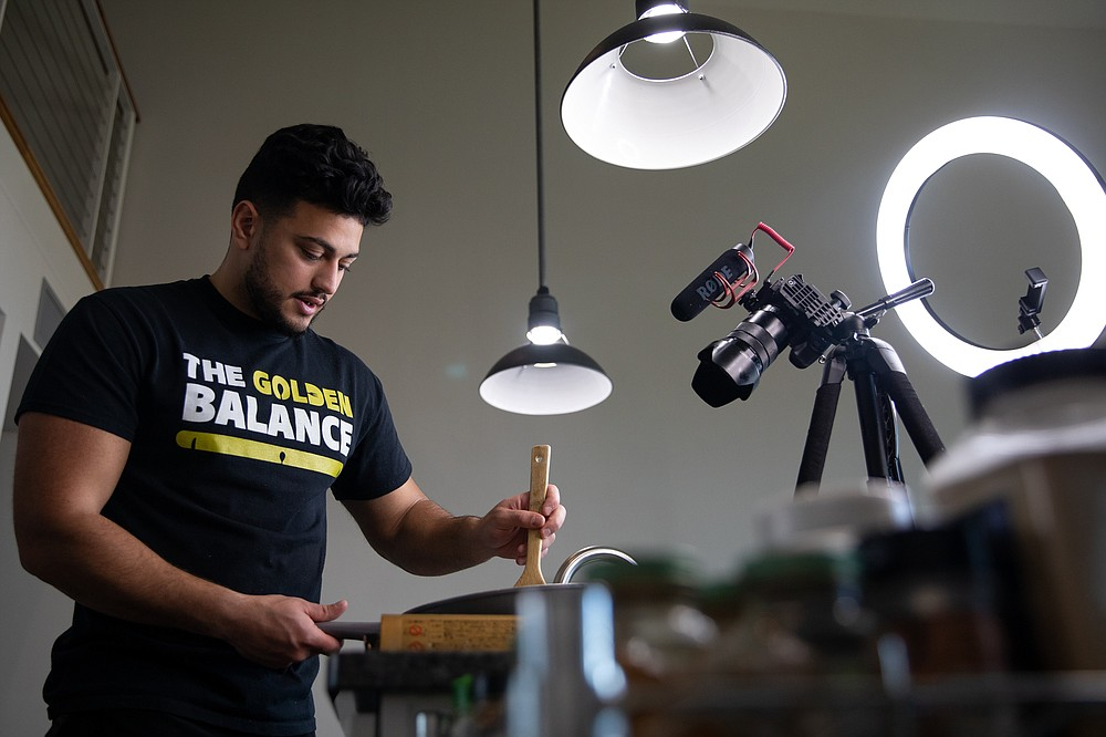 """Ahmad Alzahabi, who runs his own food media company called the Golden Balance, films a cooking video at his home in Flint, Mich., May 17, 2021. """"Recipes that are going viral on other social platforms are just visually appealing, you drool over them, but you never make them,"""" said Alzahabi. """"TikTok has allowed people to document their family gatherings, what they make at home. It doesn't have to look as pretty."""" (The New York Times/Emily Elconin)"""