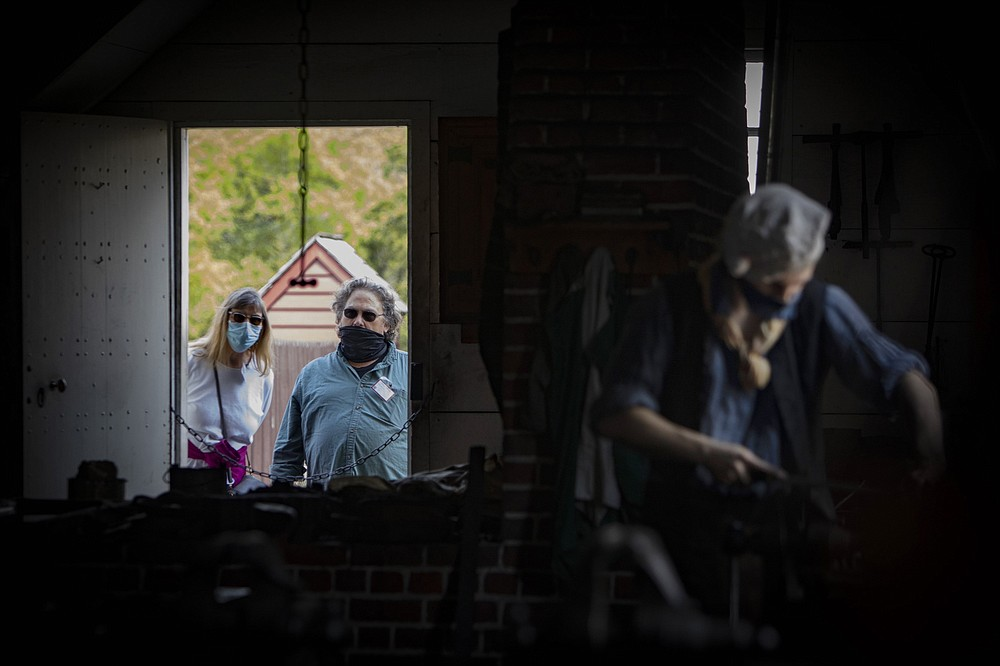 Visitors watch as Broadus Thompson works in the blacksmith shop. (For The Washington Post/Julia Rendleman)