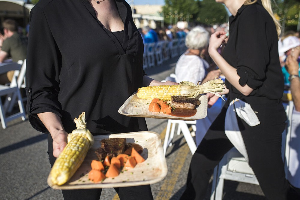 NWA Democrat-Gazette/CHARLIE KAIJO Athena Gay of Tie 1 On catering serves a Kansas City strip loin with corn on the cob, glazed-roasted carrots and MJ BBQ sauce, Saturday, June 9, 2018 on Emma Ave. in Springdale.   Back for its 3rd year, this popular event brought hundreds of guests together for a lively, friendly community dinner of multiple courses served under the night sky—right down the middle of Emma Avenue. Past attendees raved about the special experience of dining al fresco with family and friends, as well as meeting new neighbors.