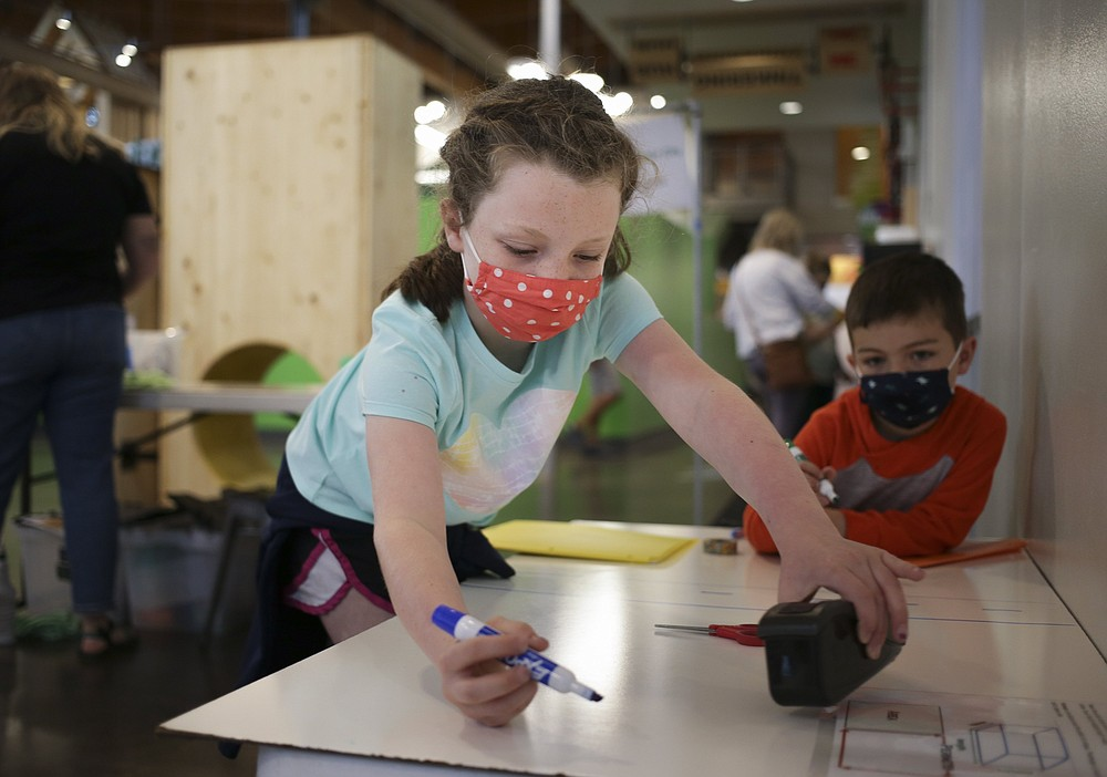 Campbell Couch (left) and Elliott Couch, 4, both of Grapevine, Texas, make their own city design using crafting tools at the Amazeum in Bentonville. Summer campers can learn about being an architect — or a marine biologist or astronaut or game developer — at the Bentonville children's museum.  (NWA Democrat-Gazette File Photo/Charlie Kaijo)