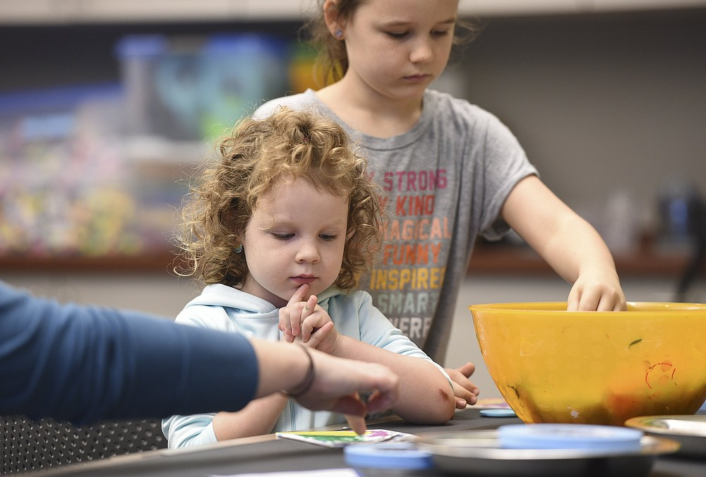 Palmer Boggs (left) and Scarlett Boggs, both of Paragould, work on a craft at Crystal Bridges Museum of American Art in Bentonville. The museum will offer a variety of summer art camps starting June 14.  (NWA Democrat-Gazette File Photo/Charlie Kaijo)