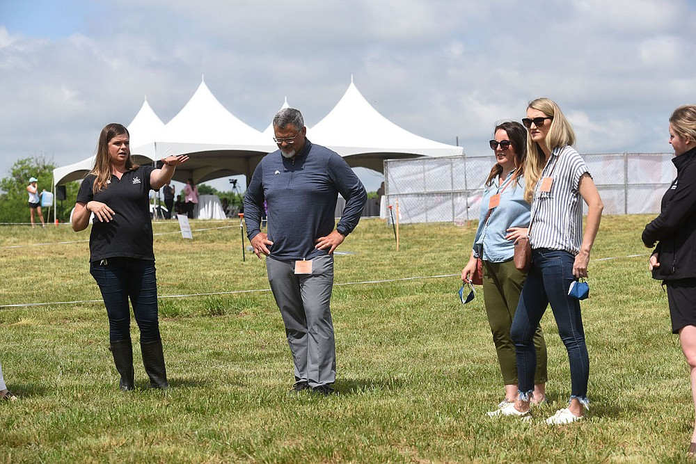 PET RESOURCE CENTER GROUNDBREAKING Kristin Switzer with Best Friends Animal Society shows guests around the grounds on Wednesday during groundbreaking ceremonies for Best Friends Animal Society's Best Friends Pet Resource center on Melissa Drive in Bentonville. Construction of the $14.5 million center will start soon at the center's six acres. Resources will include a pet medical clinic offering low-cost services to income-qualifying families, life saving efforts for pets in Northwest Arkansas shelters that are of greatest risk and help for owners struggling to keep their pets. The center will have a pet supply pantry, foster care for pets that need extra training, volunteer programs, education programs and more. Best Friends Animal Society was founded 35 years ago with headquarters in Utah. The society hopes to end the killing of dogs and cats in the United States by 2025. Go to nwaonline.com/210527Daily/ to see more photos. (NWA Democrat-Gazette/Flip Putthoff)