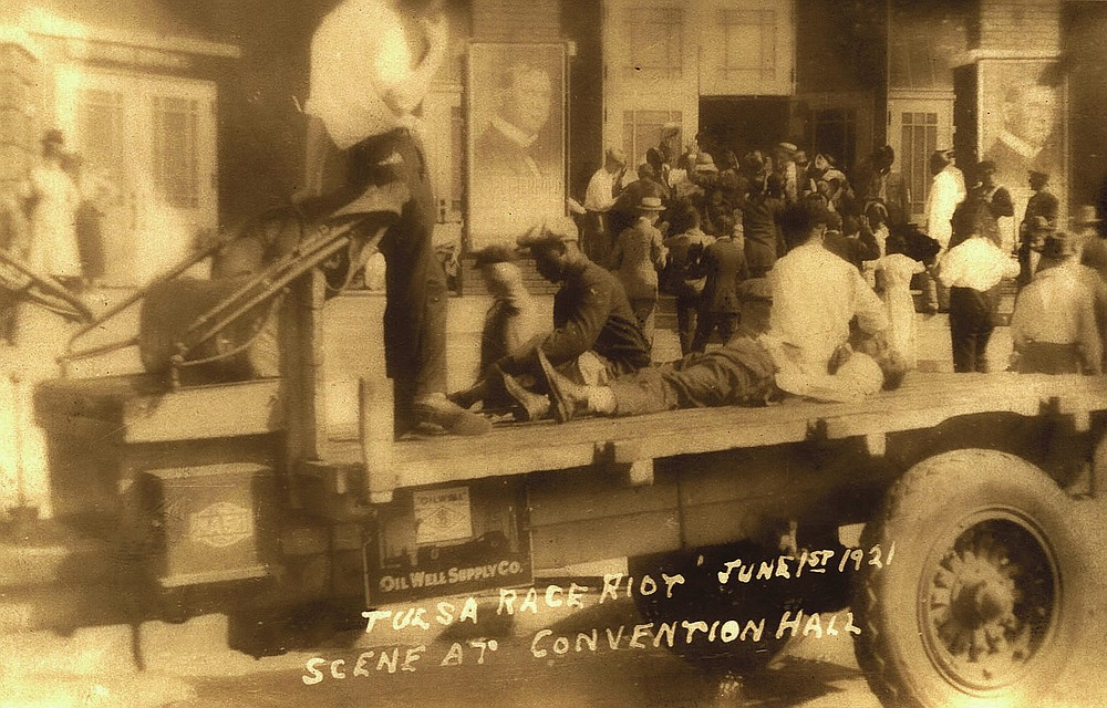This postcard provided by the Department of Special Collections, McFarlin Library, The University of Tulsa shows a truck parked in front of the Convention Hall, with a man whose condition is unknown, lying on the bed of the truck, and two others sit to either side. A man in civilian attire stands guard over them during the Tulsa Race Massacre June 1, 1921, in Tulsa, Okla. (Department of Special Collections, McFarlin Library, The University of Tulsa via AP)