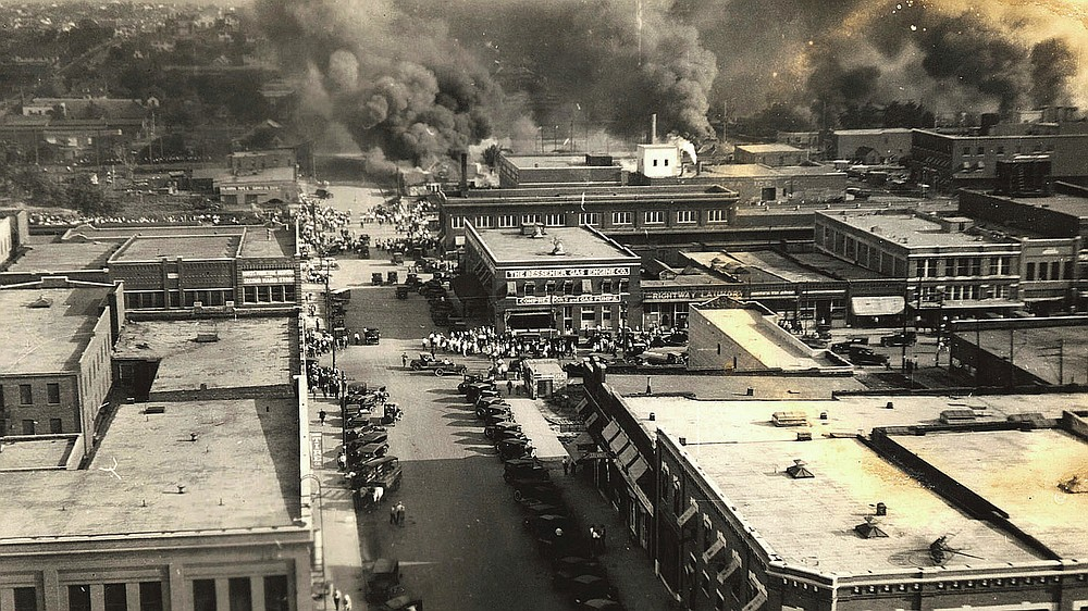 This photo provided by Department of Special Collections, McFarlin Library, The University of Tulsa shows crowds of people watching fires during the June 1, 1921, Tulsa Race Massacre in Tulsa, Okla. (Department of Special Collections, McFarlin Library, The University of Tulsa via AP)