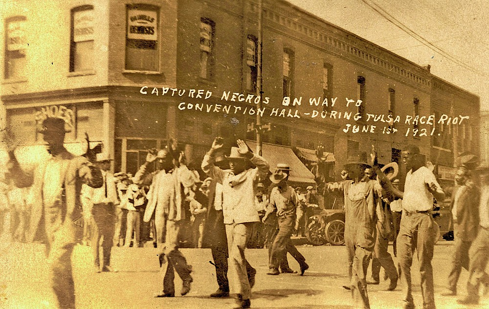 In this photo provided by the Department of Special Collections, McFarlin Library, The University of Tulsa, a group of Black men are marched past the corner of 2nd and Main Streets in Tulsa, Okla., under armed guard during the Tulsa Race Massacre on June 1, 1921. (Department of Special Collections, McFarlin Library, The University of Tulsa via AP)