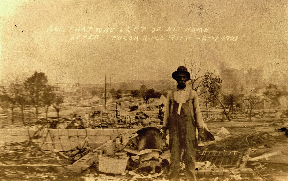 This photo provided by the Department of Special Collections, McFarlin Library, The University of Tulsa shows an unidentified man standing alone amid the ruins of what is described as his home in Tulsa, Okla., in the aftermath of the June, 1, 1921, Tulsa Race Massacre. (Department of Special Collections, McFarlin Library, The University of Tulsa via AP)
