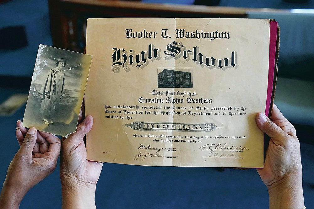 A graduation photo and the high school diploma of Tulsa Race Massacre survivor Ernestine Alpha Gibbs are pictured during an interview with her descendants, Sunday, April 11, 2021, in Tulsa, Okla. (AP Photo/Sue Ogrocki)