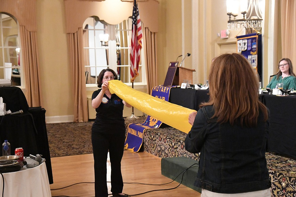 Casey Wylie, director of education at Mid-America Science Museum, does a science demonstration with Diane LaFollette, executive director of the museum, at Hot Springs National Park Rotary Club on Wednesday. - Photo by Tanner Newton of The Sentinel-Record