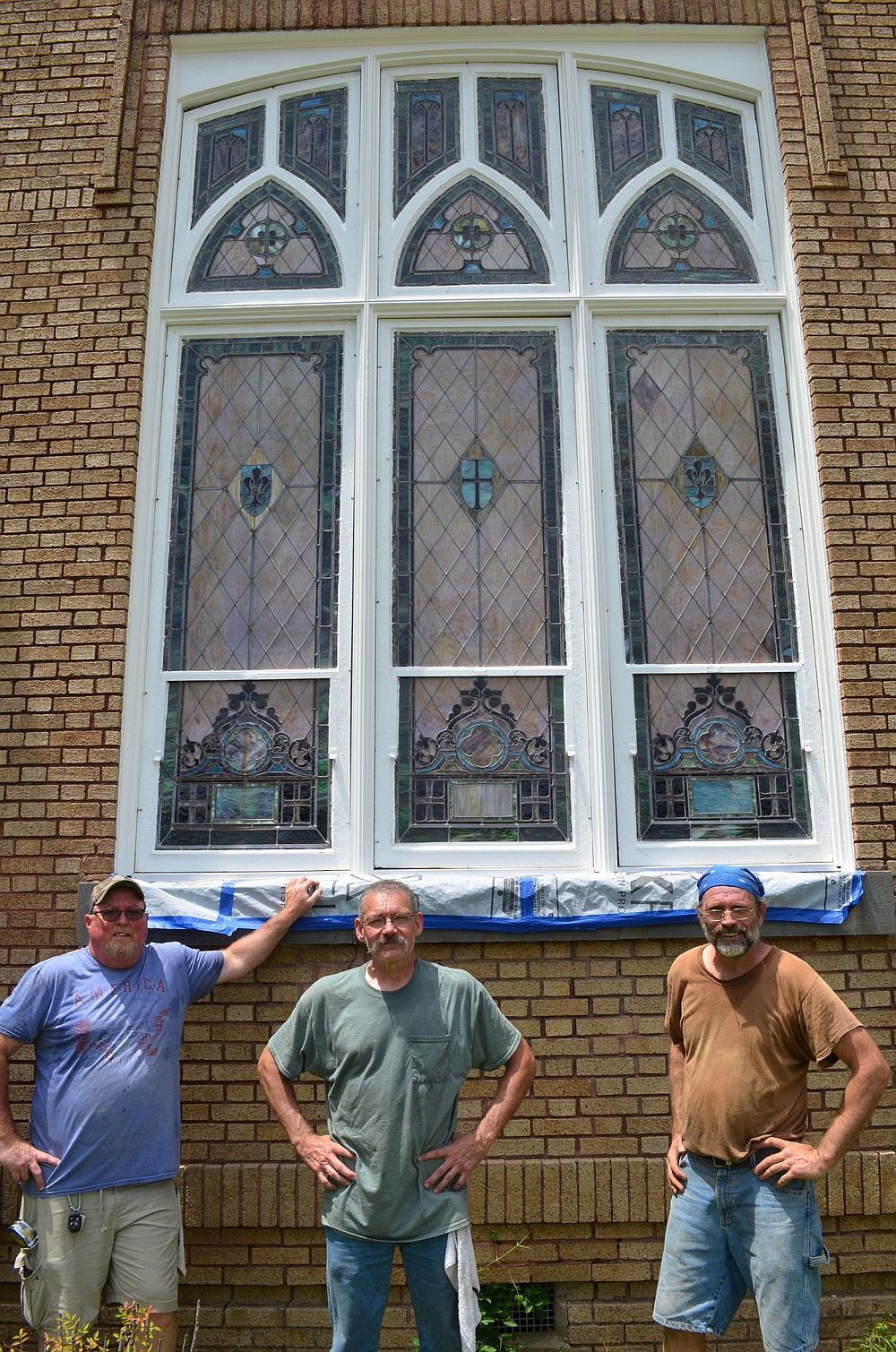 (Left to right) Ron Dwarshak, Nathan Cathey and Ernest Waters catch their breath after reinstalling freshly renovated 1912 period Murano stained glass in newly reconstructed wooden frames.  (Special at The Commercial / Richard Ledbetter)