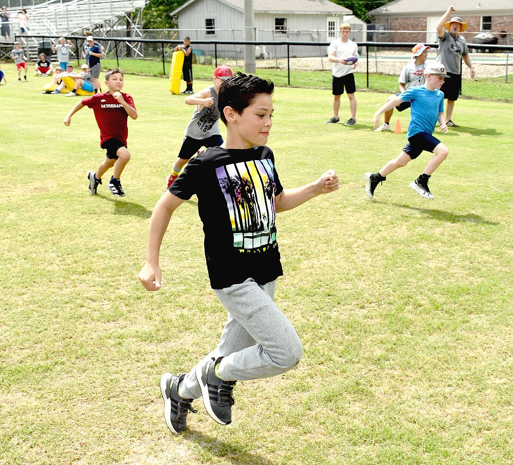 """MARK HUMPHREY  ENTERPRISE-LEADER/Prairie Grove rising fourth grader Carter Lisir crosses the finish line first as Prairie Grove head football coach Danny Abshier (upper right) pumps a fist. Carter won the fourth grade sprint by such a margin that assistant coach Mason Pinkley said, """"he smoked them by a country mile."""""""
