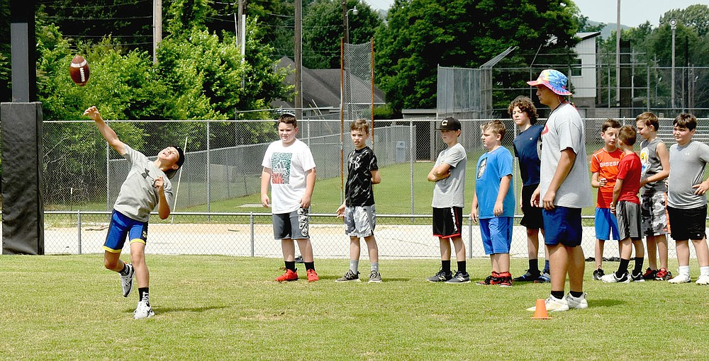 MARK HUMPHREY  ENTERPRISE-LEADER/Prairie Grove rising fifth grader Cash Oxford throws the football during the punt, pass and kick portion of Prairie Grove's annual pee wee football camp held last week at Tiger Den Stadium.