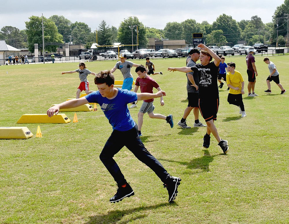 MARK HUMPHREY  ENTERPRISE-LEADER/Prairie Grove rising seventh grader Chantry O'Brien works his way across the field while practicing football skills during a recent pee wee camp conducted by the Tiger varsity football coaches.