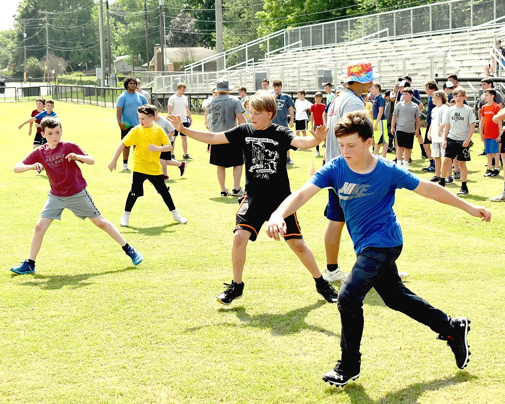 MARK HUMPHREY  ENTERPRISE-LEADER/A quartet of future Prairie Grove Tigers (from left): Copeland Myers (rising fourth grader), Noah Barnes (rising fifth grader), Mayson Chronister (rising sixth grader), and Chantry O'Brien (rising seventh grader) work on their footwork on Wednesday, June 9 at Prairie Grove's pee wee football camp.