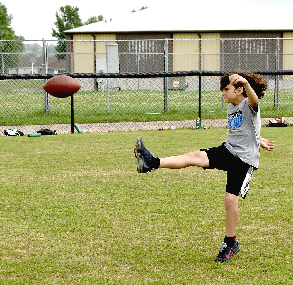 MARK HUMPHREY  ENTERPRISE-LEADER/Skyler Clinkscales punts the football during the punt, pass and kicking portion of Prairie Grove's annual pee wee football camp held last week at Tiger Den Stadium.