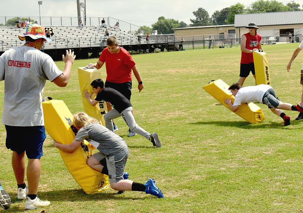 MARK HUMPHREY  ENTERPRISE-LEADER/Learning to tackle correctly is a basic football skill taught at last week's annual Prairie Grove pee wee football camp.