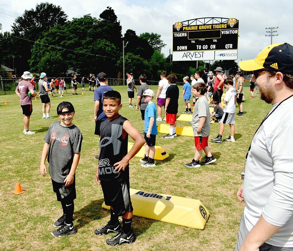 MARK HUMPHREY  ENTERPRISE-LEADER/Prairie Grove rising fifth grader Zayland Chronister (left) and Aiden Wilson, a rising seventh grader, eagerly prepare for the next drill while assistant coach Nik Paroubek supervises. The boys were among 170 youth  attending Prairie Grove's pee wee football camp last week.