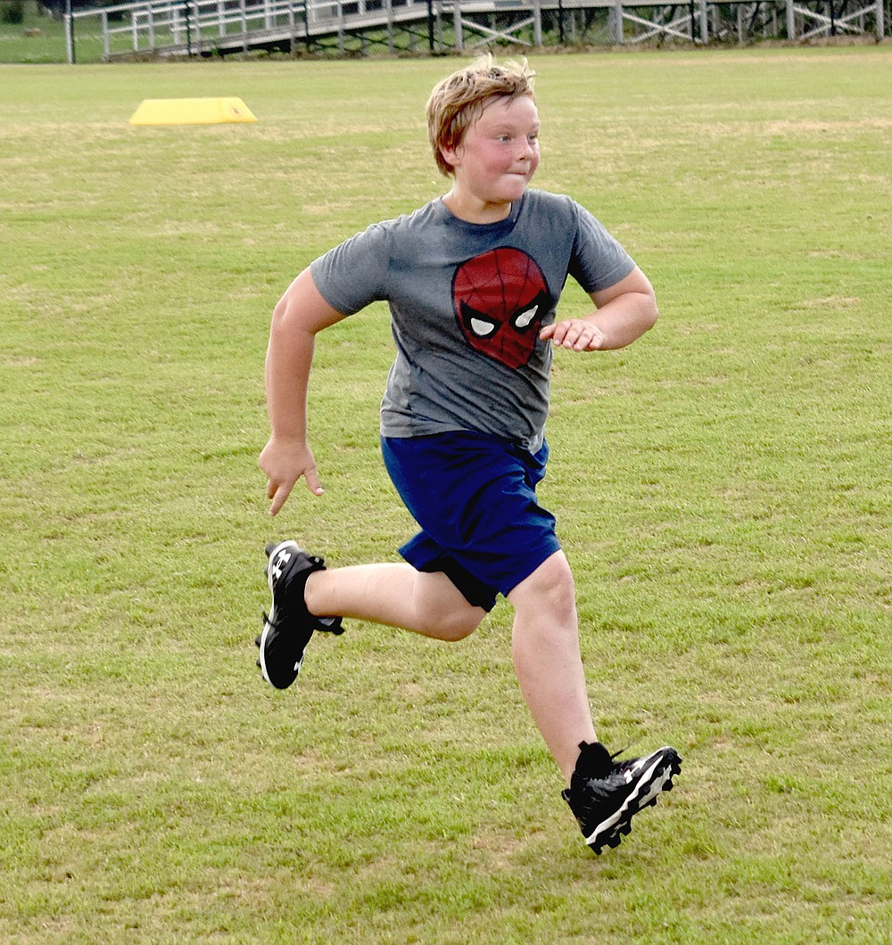 MARK HUMPHREY  ENTERPRISE-LEADER/Prairie Grove rising sixth grader Kristopher Phipps sprints in the footsteps of legendary Tigers, who preceded him in the school's football program which has thrived under head coach Danny Abshier since he took over in 1993.