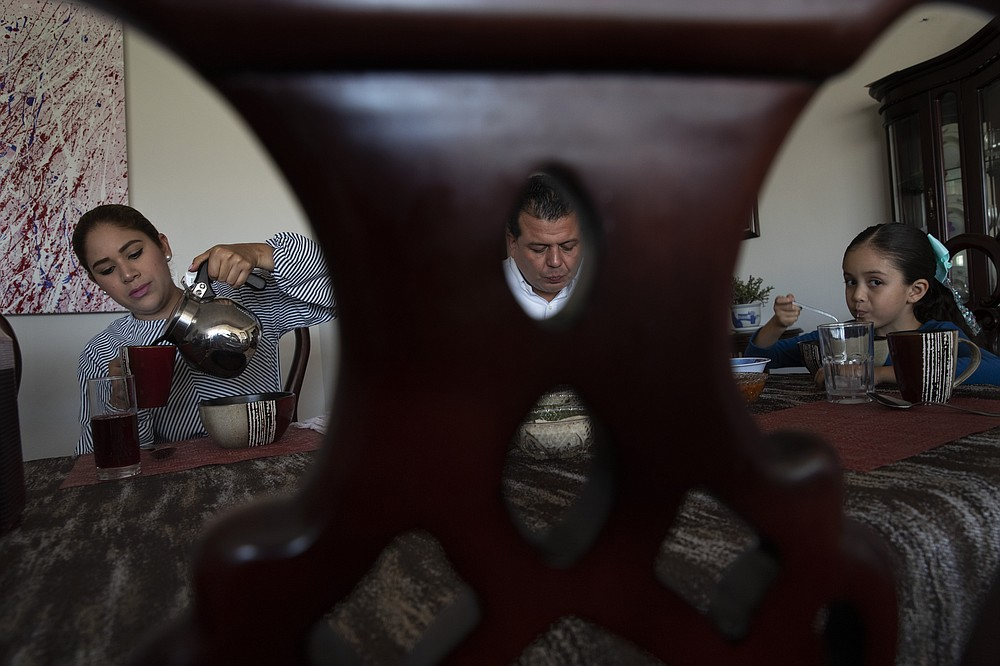 Photographed through the backrest of a chair, mayoral candidate Guillermo Valencia with the Institutional Revolutionary Party, PRI, has breakfast with his family at their home in Morelia, Michoacan sate, Mexico, Saturday, May 22, 2021. Valencia was unharmed in an attempt on his life on May 8 when two people shot at the truck in which he was traveling, and now he drives with only a bodyguard because campaign supports are too scared to drive with him. (AP Photo/Marco Ugarte)